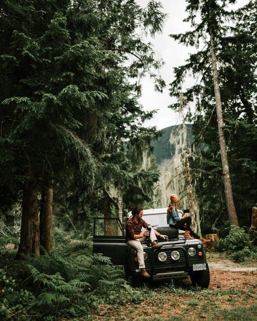 dva mladí lidé s autem v přírodě